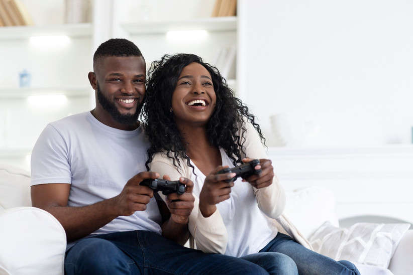 Smiling couple playing a video game together
