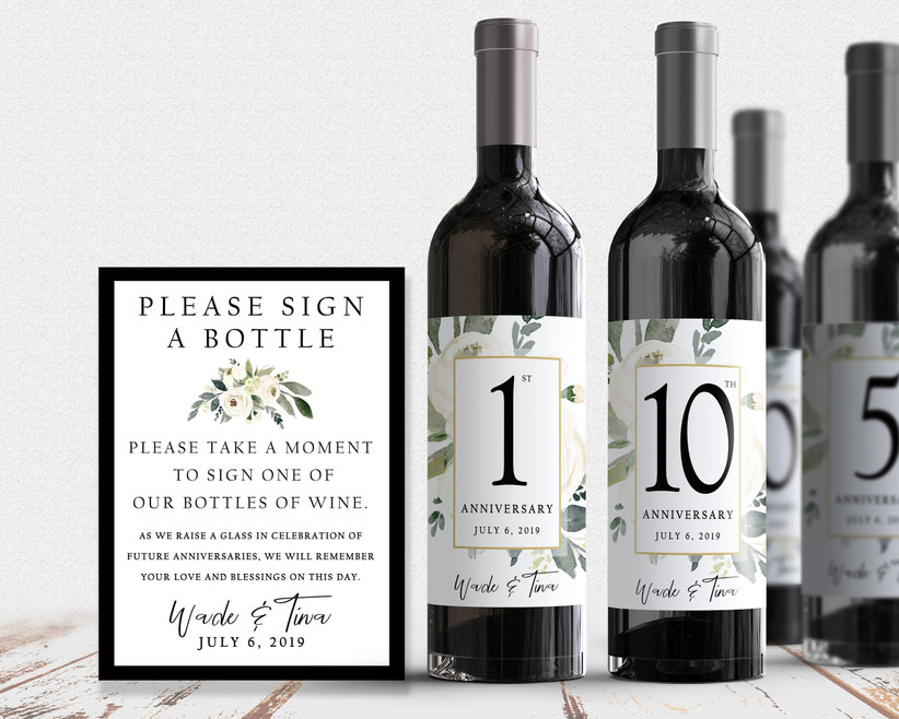 Wine bottles with custom anniversary labels for guests to sign