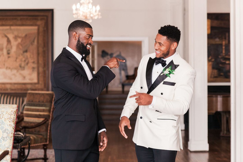 groom and his best man having candid conversation while getting ready