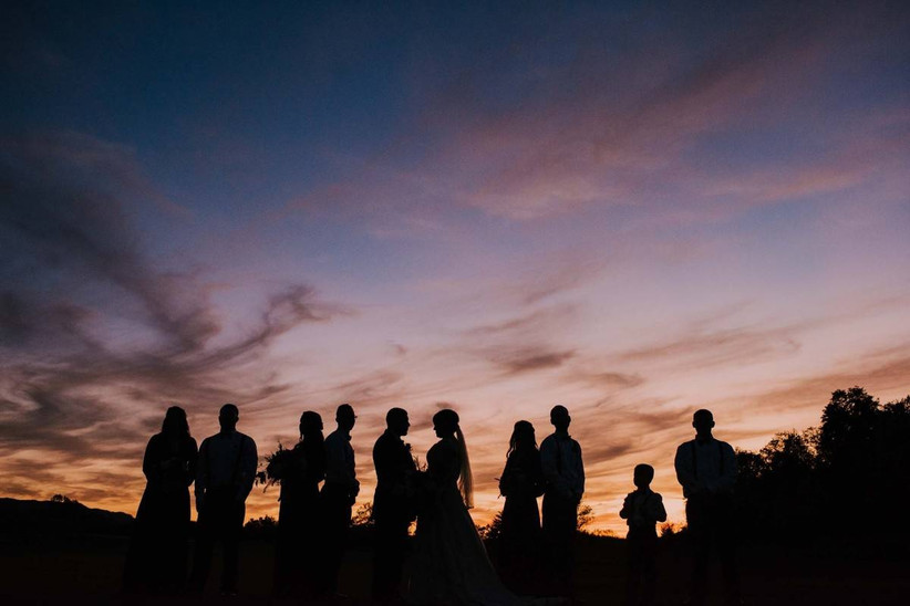silhouettes of newlyweds and their wedding party against sunset sky
