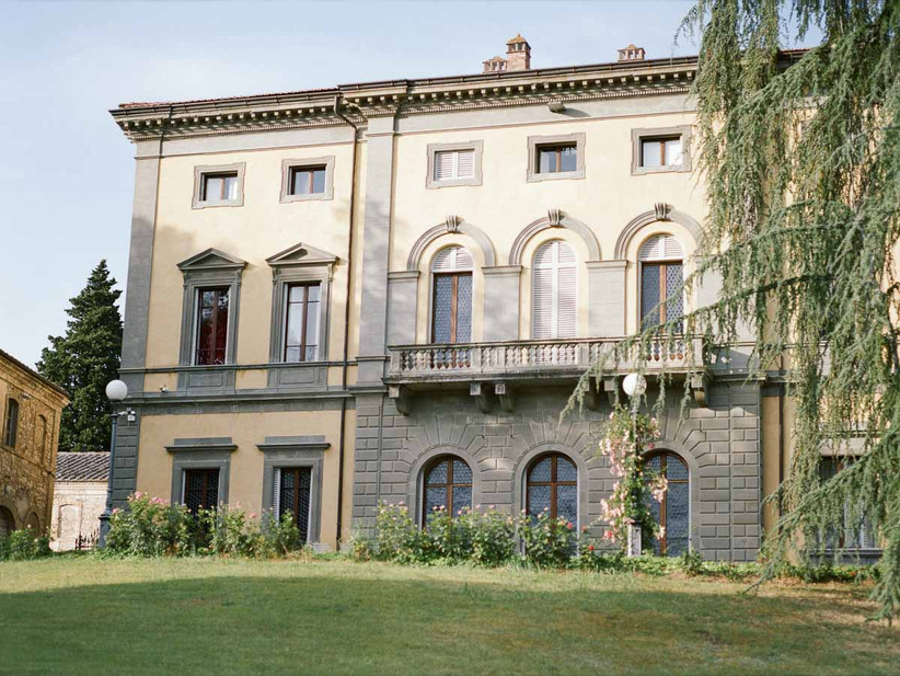 italy wedding venue private historic villa with trees and flowering bushes in front