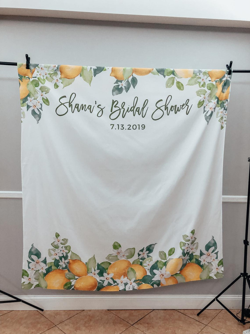 White bridal shower backdrop with lemon and greenery motif border