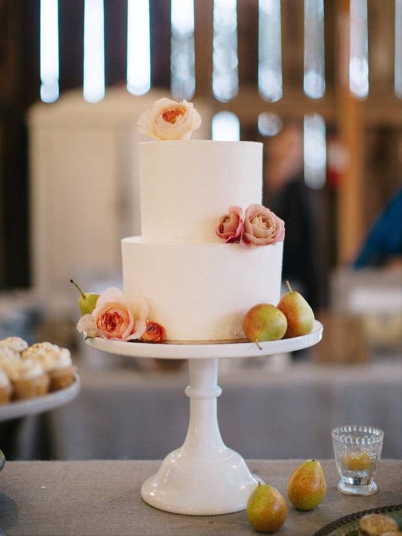elegant wedding cake decorated with miniature green pears and light pink roses