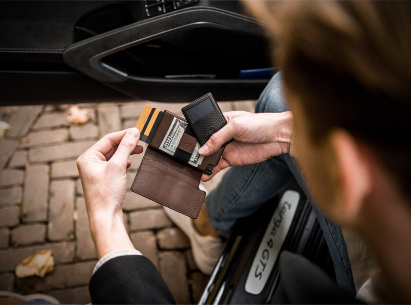 Man using leather Ekster wallet to retrieve his card