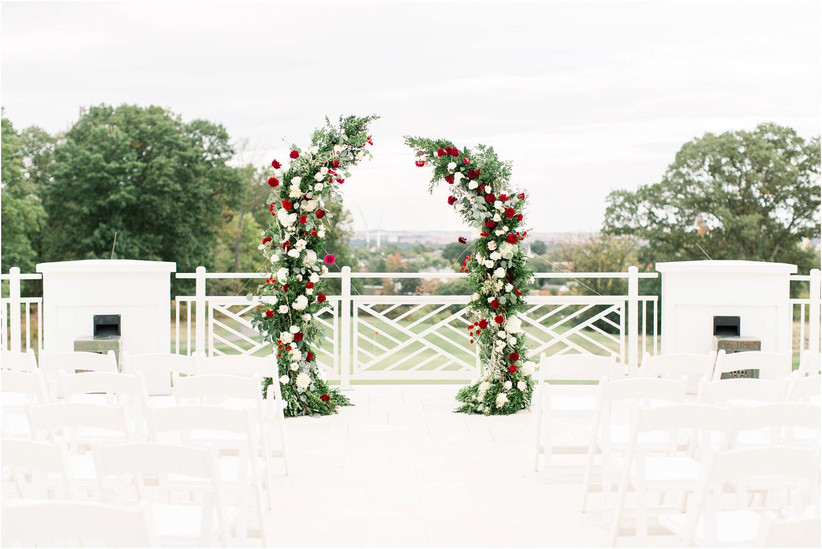 romantic wedding arch with greenery, white flowers and red roses