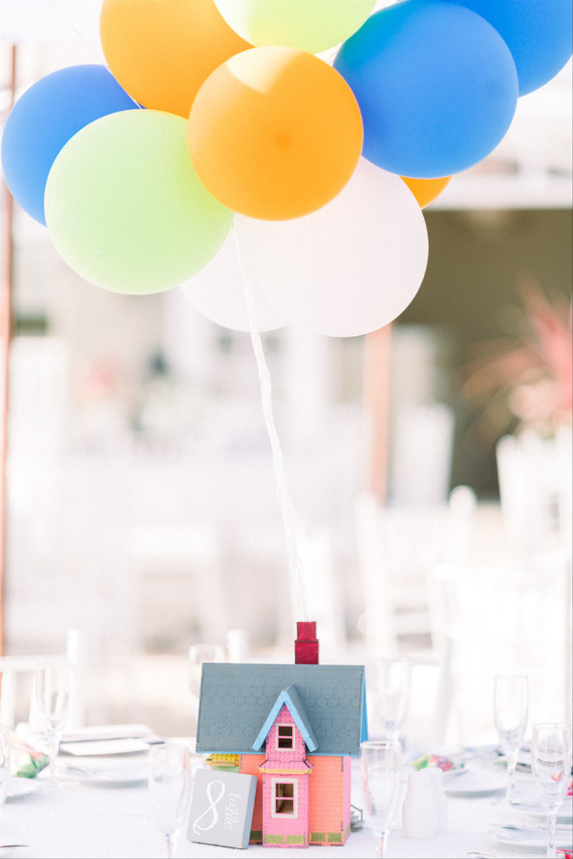 up-themed wedding centerpiece with miniature pink house and balloons