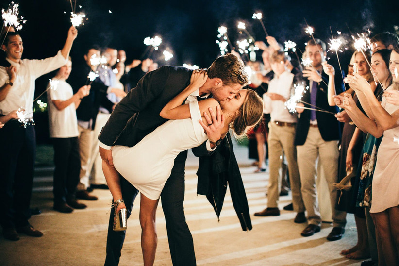 bride and groom kiss at night while wedding guests surround them with sparklers