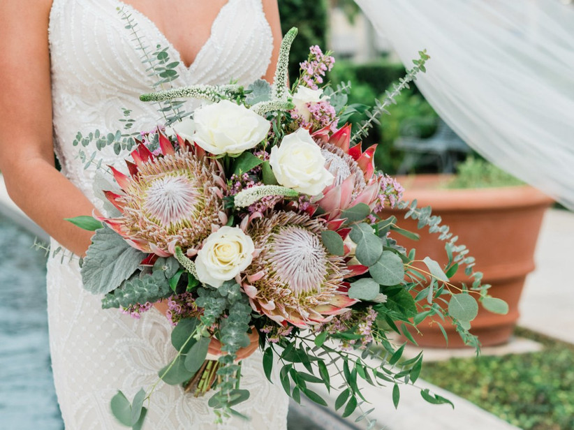 bride holding bouquet with two king proteas and eucalyptus