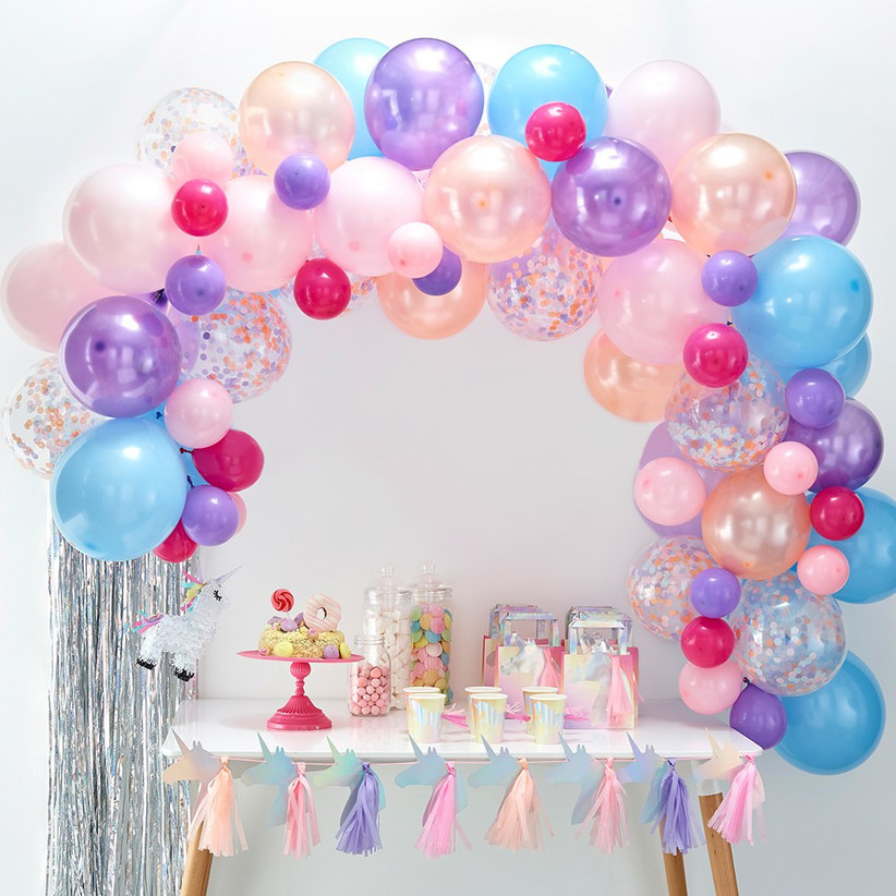 Pretty balloon garland arch in pastel hues of pink, blue, and purple arranged over a dessert table