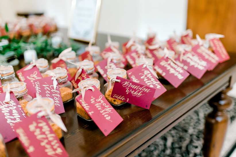 wedding favor ideas: miniature bottles of spices are lined up on a table. each one has a tag with the guest's name and reception seating assignment