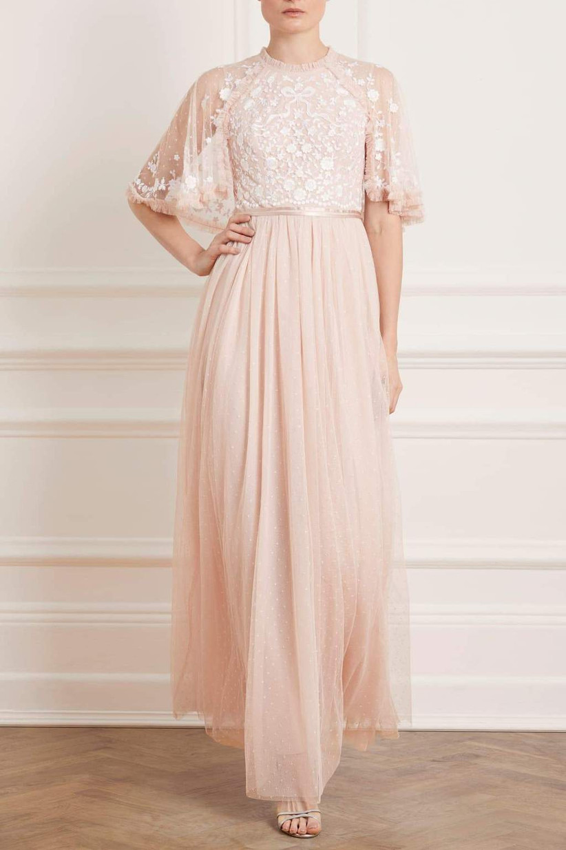 Model wearing embroidered pastel pink tulle maxi dress with cape sleeves