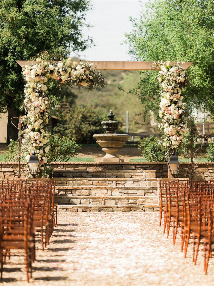 sunny outdoor wedding ceremony gravel courtyard with stone fountain with wooden arbor covered in light pink and white flowers