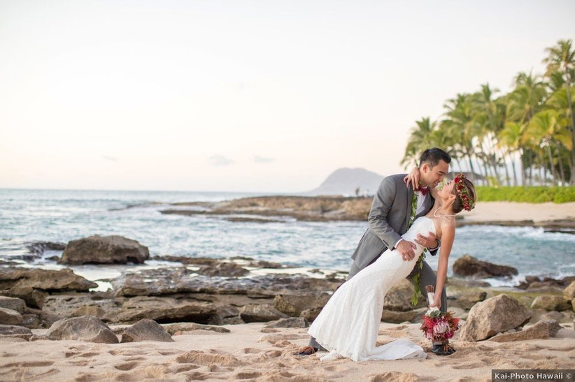 Hawaiian bride and groom standing on rocks along the ocean at sunset