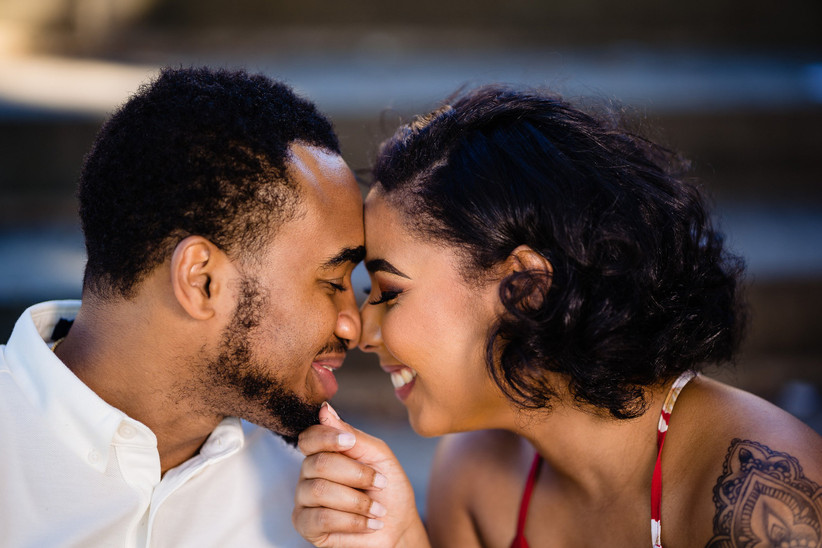 side portrait of a black couple smiling and pressing foreheads together, she has her hand on his chin