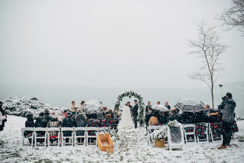 Snowy winter wedding ceremony outdoors with guests wearing plaid blankets
