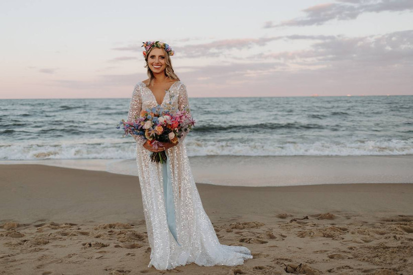 bride stands on the beach with the ocean in the background while holding a colorful bouquet and wearing matching flower crown