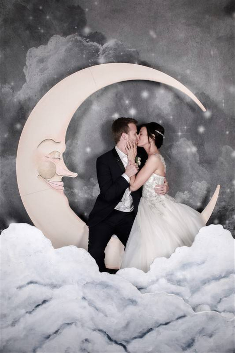 bride and groom kiss in front of oversized crescent moon paper photo backdrop