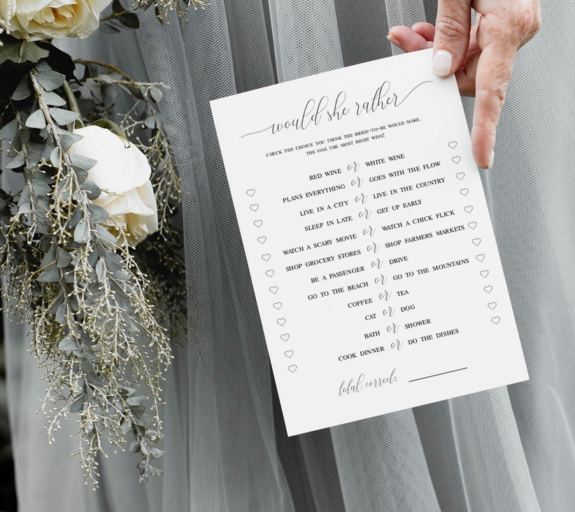 bridesmaid holds a checklist of questions printed onto paper