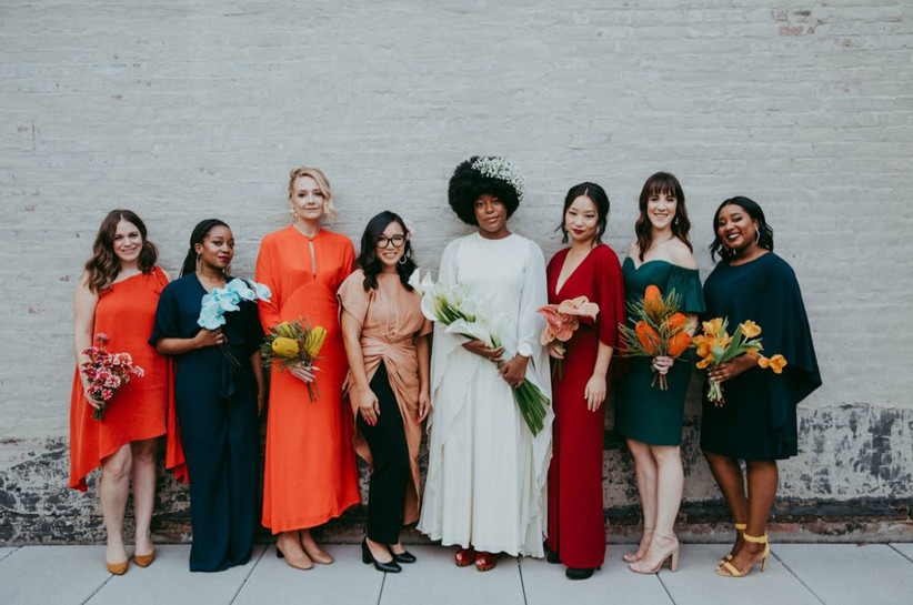 Bride wearing white posing with bridesmaids in alternating bright and dark hues