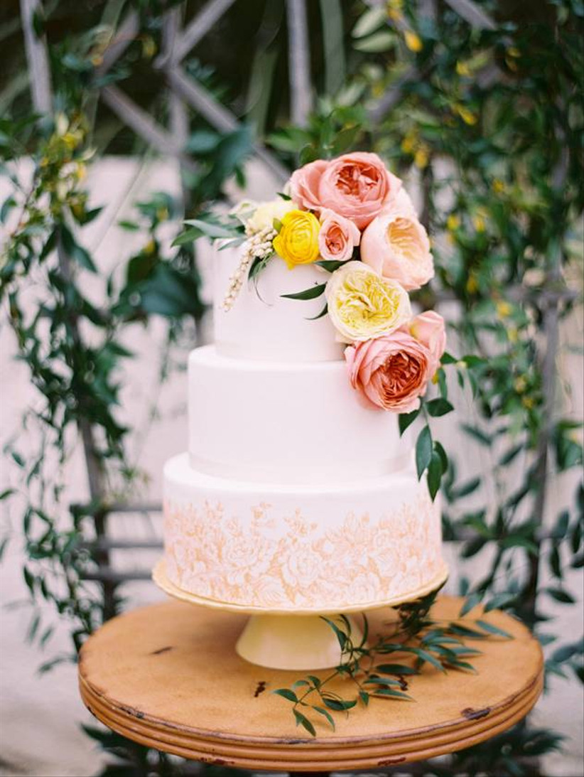 white and gold wedding cake with floral print decorating the bottom tier