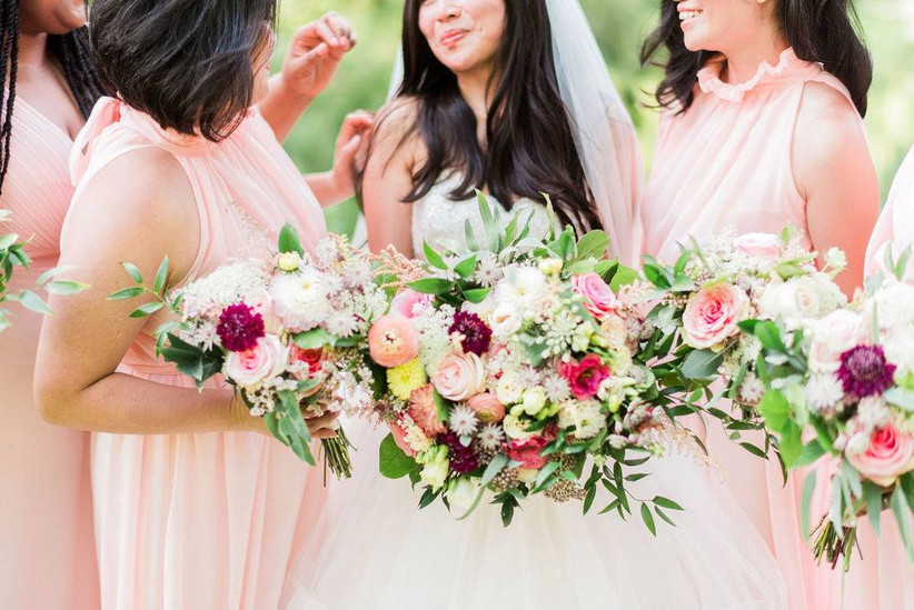 bride stands next to bridesmaids holding matching bouquets