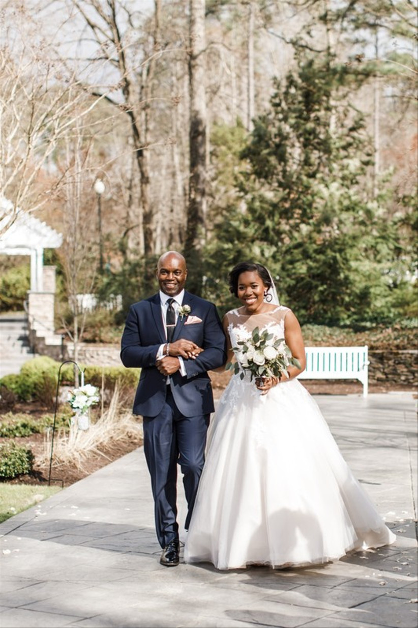 Black bride walks down the aisle of outdoor wedding ceremony with her father. She is wearing a tulle ball gown with illusion lace neckline