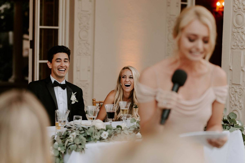 bride and groom laugh hysterically while maid of honor gives a speech