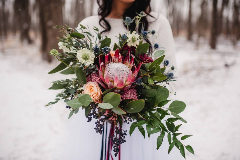 winter protea bouquet with scabiosa, greenery, and viburnum berries