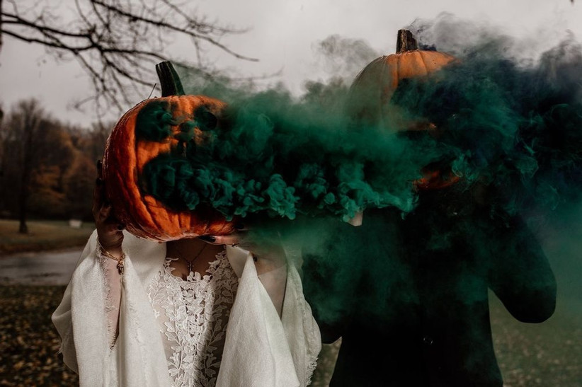 bride and groom holding jack o lanterns in front of their faces with dark green smoke coming out of the pumpkins