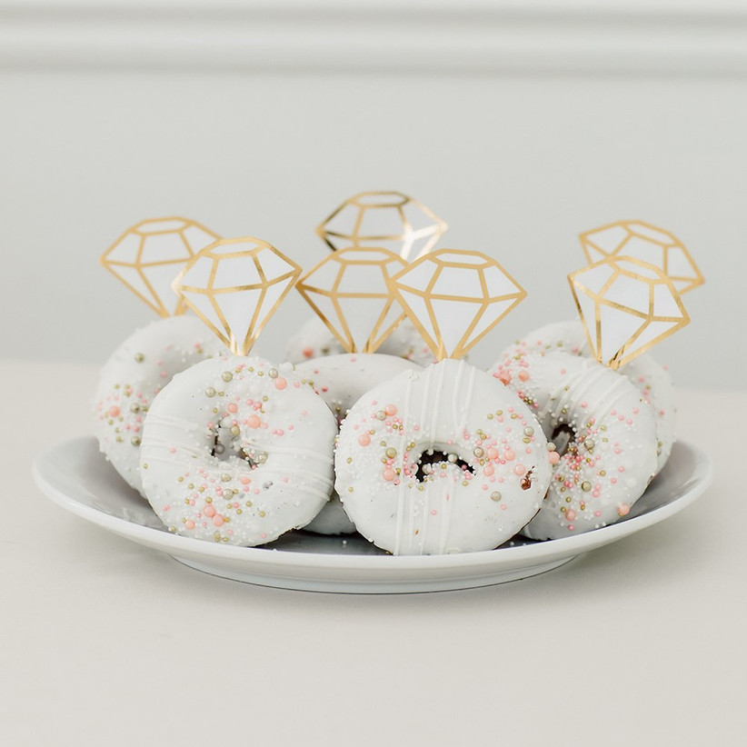 Plate of delicious donuts with white icing, pretty sprinkles, and diamond cake toppers