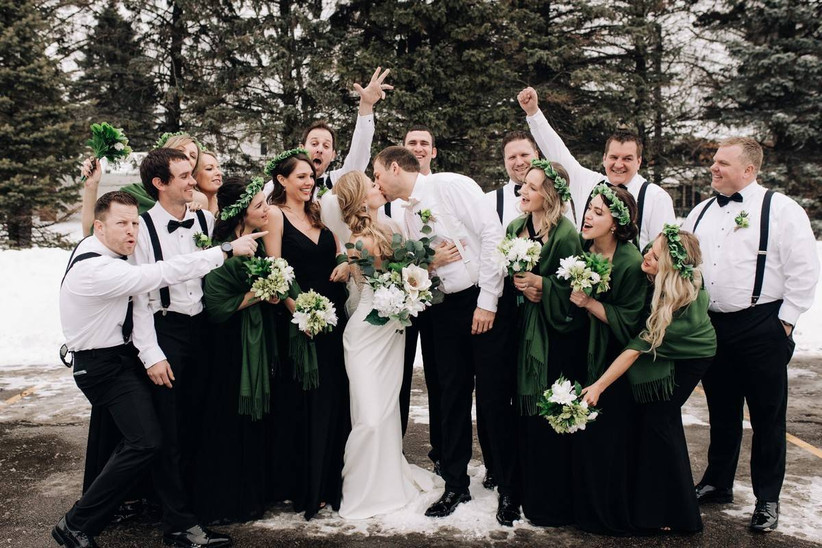 wedding party surrounds couple and cheers as they kiss