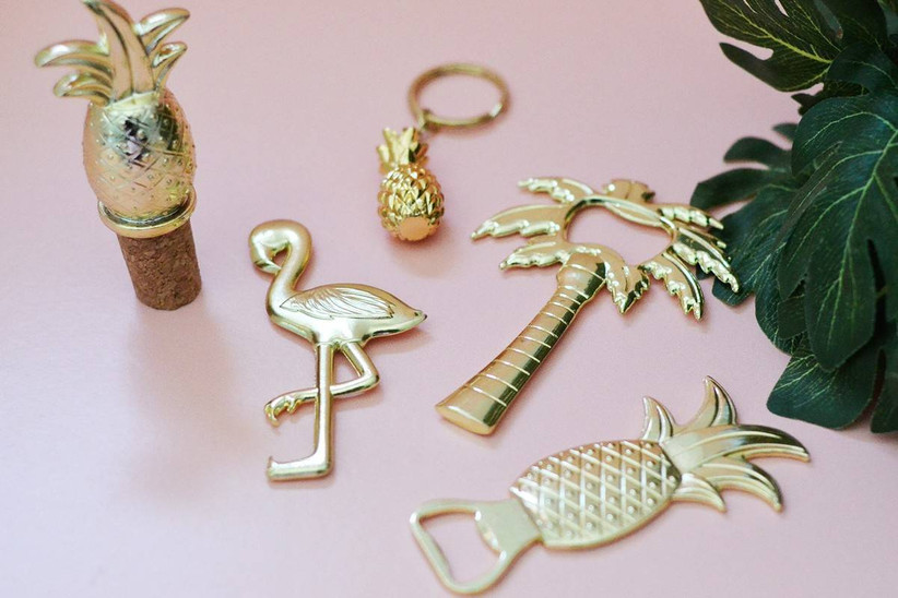 gold tropical themed bottle openers in the shape of flamingos, pineapples and palm trees