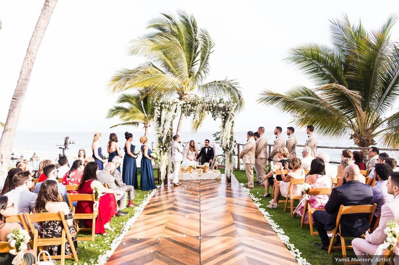beach wedding ceremony with palm trees and ocean backdrop