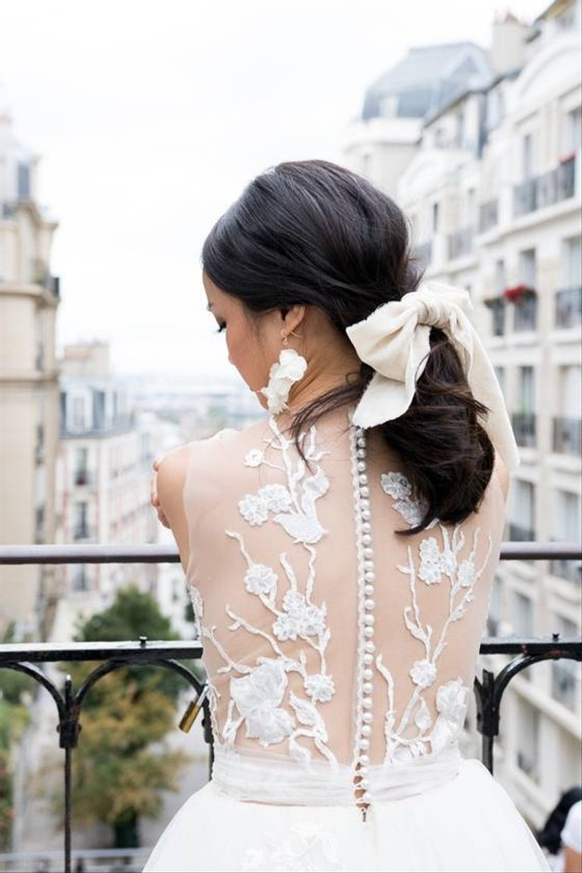 photo of a bride from behind. she is standing on a balcony overlooking paris with her hair in a low ponytail tied with a white silk bow