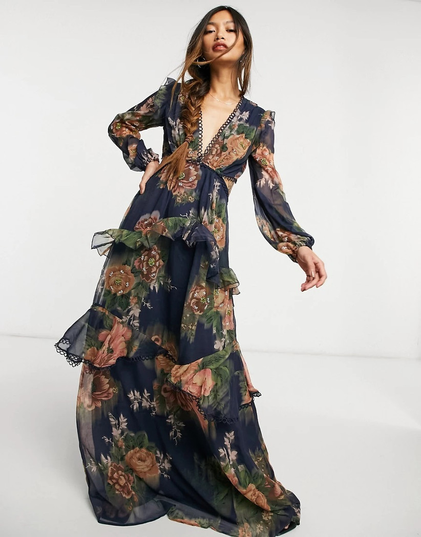Model wearing navy maxi with ruffled tiers and terracotta floral print