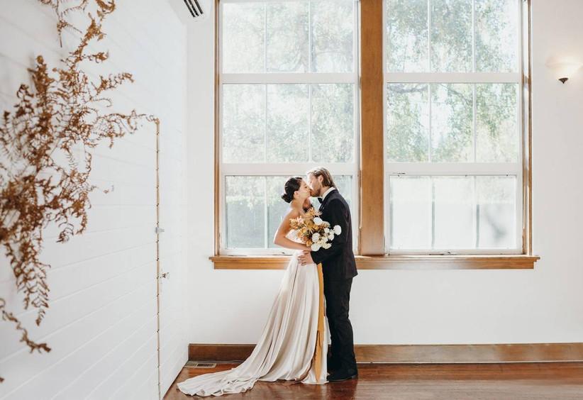 bride and groom kiss in front of windows at historic portland oregon wedding venue vintage schoolhouse with hardwood floors