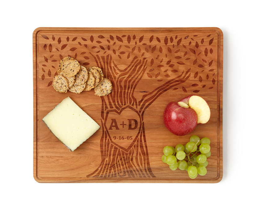 Custom engraved wooden serving board with a couple's initials carved into a tree design with meaningful date
