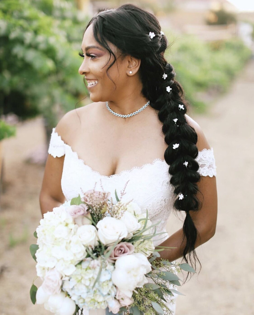 bride with long brown hair wears side fishtail braid decorated with small flowers