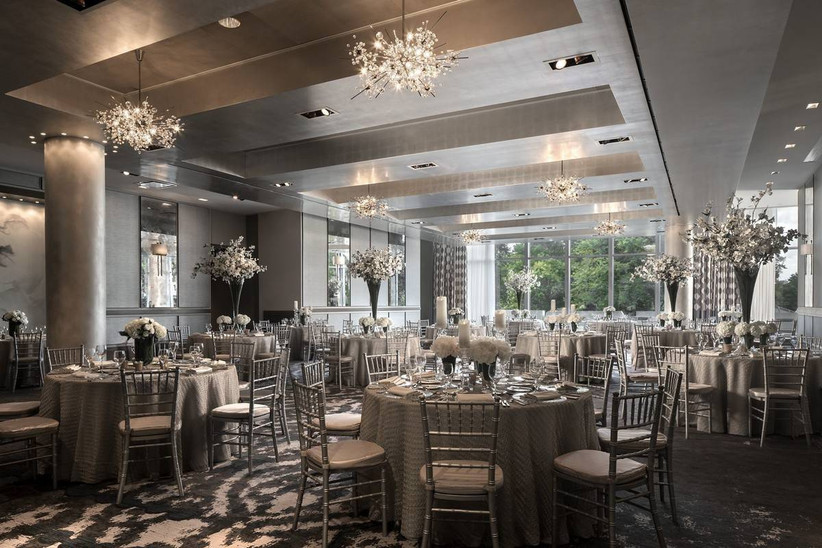 contemporary ballroom boston wedding venue decorated in silver and gray tones with chandeliers, round tables and wraparound windows
