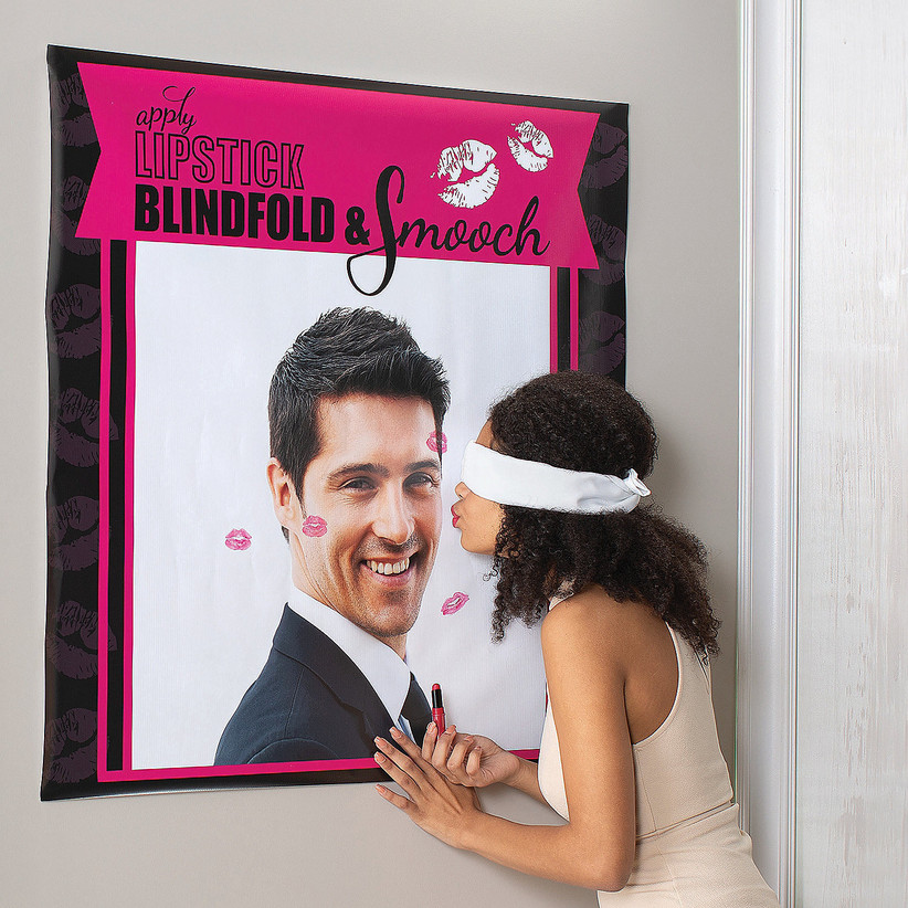 blindfolded woman tries to kiss the groom's picture