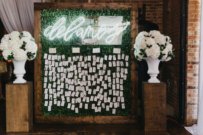 greenery wall with white neon sign of couple's last name and escort cards hanging underneath