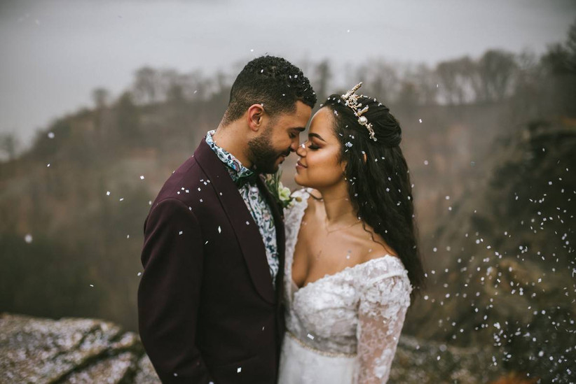 Bride and groom stand face to face with their eyes closed as they are showered with white confetti