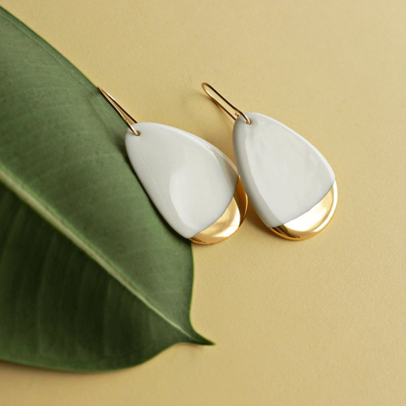 white and gold drop earrings set against a leaf backdrop