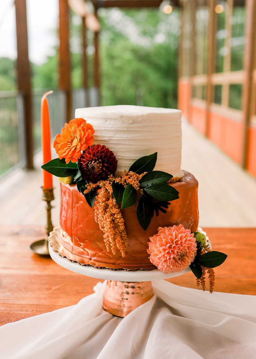 two-tier cake with orange bottom tier and orange flowers decorating the side