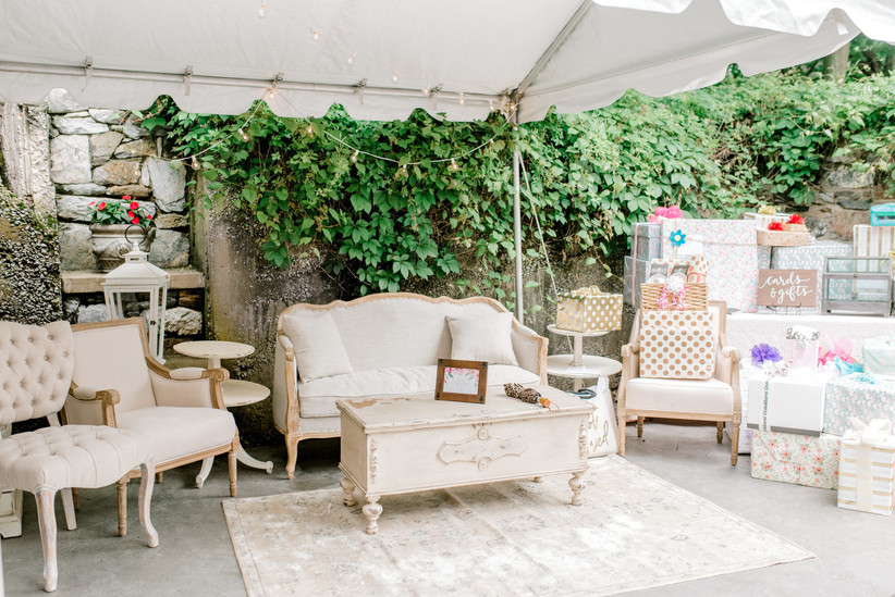 outdoor bridal shower with loveseat surrounded by gift boxes