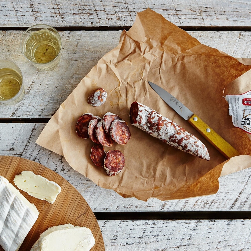 Salami sliced on brown paper with a wooden-handle knife
