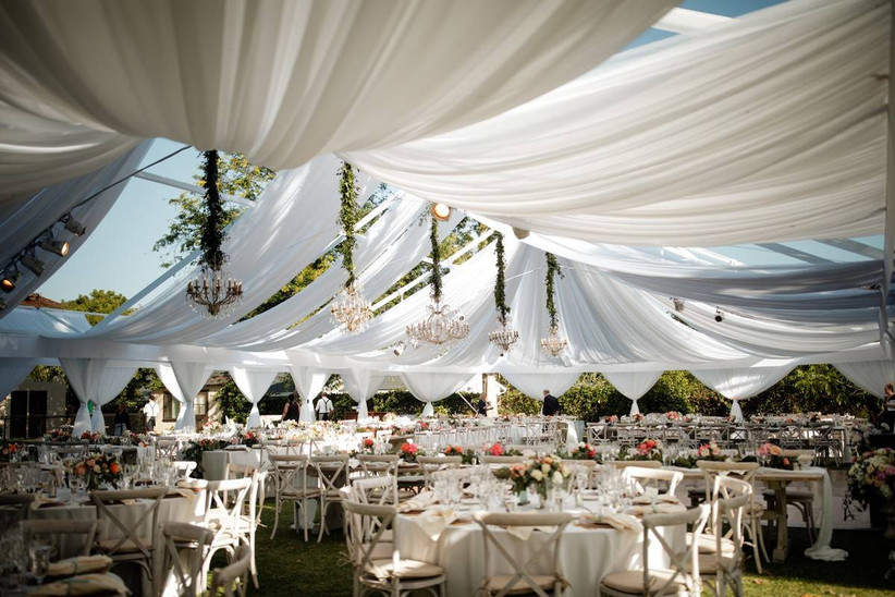 tented wedding decorated with white draped fabrics chandeliers and greenery