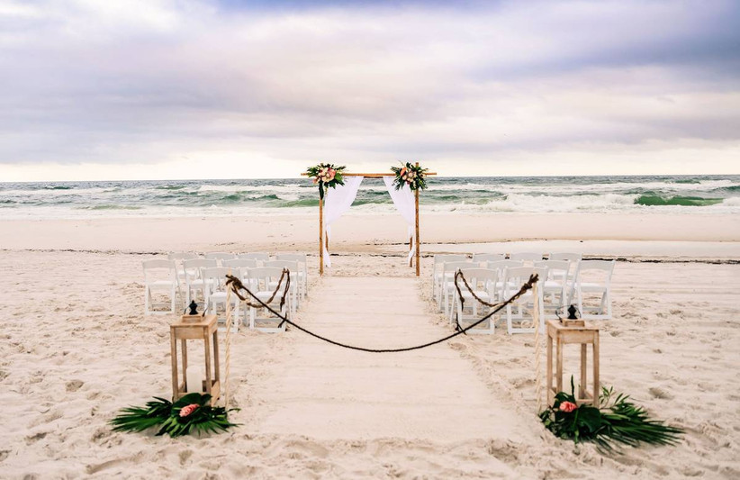 beach wedding ceremony with vintage lanterns on either side of the aisle and floral wooden arch at the altar