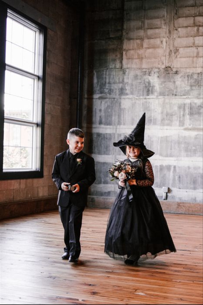 flower girl wearing black tulle dress and witch hat walks down the aisle with ring bearer