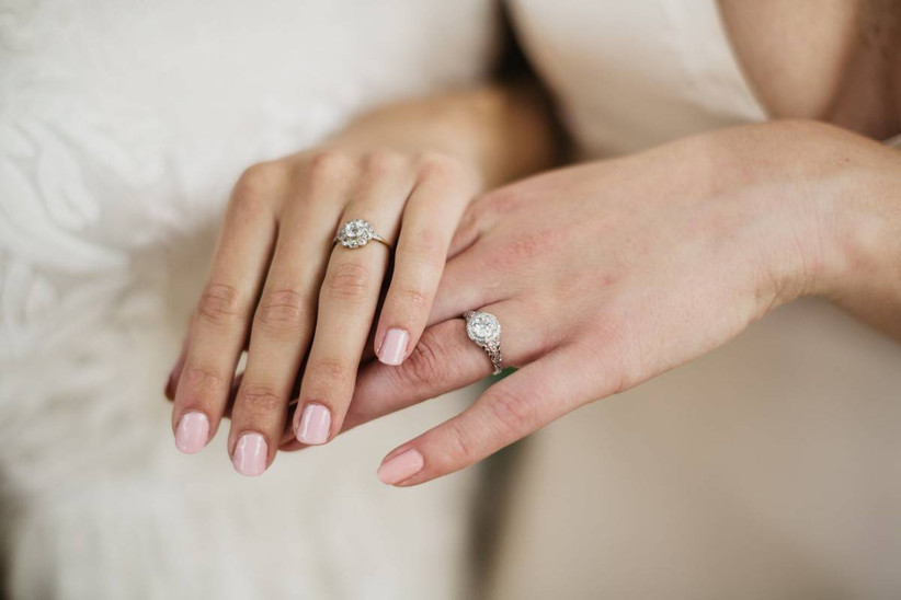 two brides showing their engagement rings